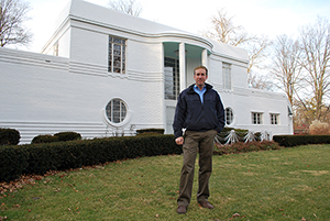Jeff McCoy stands in front of the T.G. Wilkinson House, which he bought last year and is in the process of restoring. The Art Moderne-style home is constructed of steel-reinforced concrete faced with brick veneer that has been painted white, an element of the original design. Photo Courtesy Indiana Landmarks.