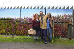 Dan Coe, center, stands with the assistants who helped him paint the fireweed mural, Karen Simpson, left, and daughter Rachel Coe, right. The six-panel mural shows the progression of fireweed from flower to fluff over the growing season. Image by Michael Walsh.