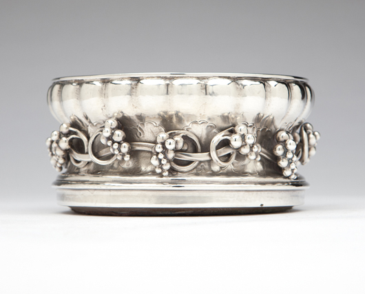 """Estimated at $6,000-$9,000, this early Georg Jensen """"Grape"""" wine coaster, dated 1919, leads a large selection of items by the Danish master of modern silver design. John Moran Auctioneers image."""