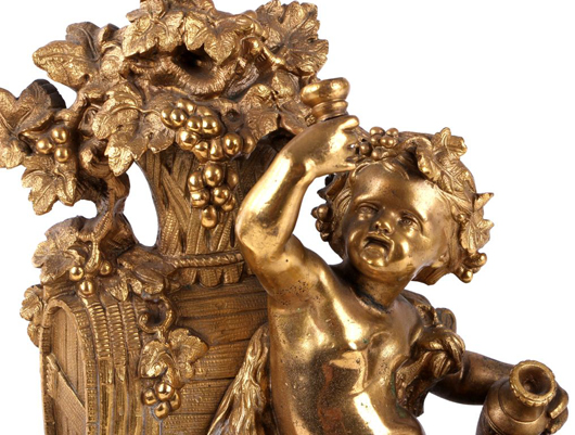 Lot 187: pair of Louis XV-style bronze doré chenets and fender depicting bacchanalian putti (detail). Gray's Auctioneers and Appraisers image.