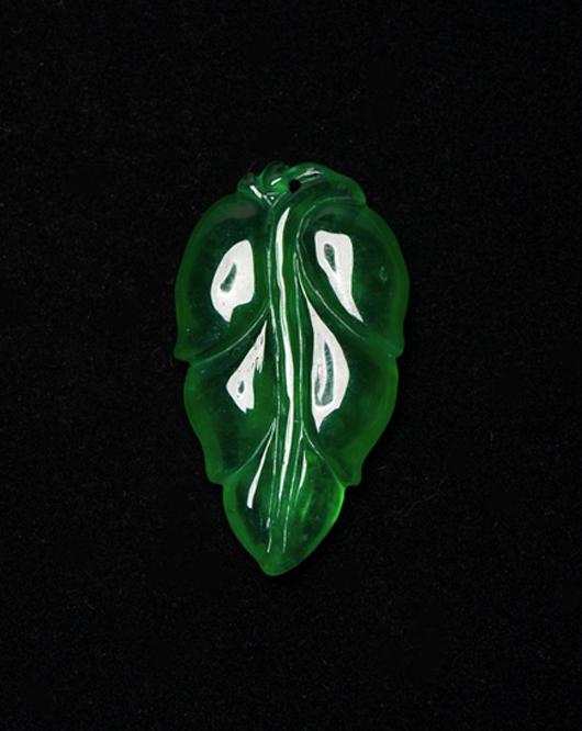 Lot 128: Chinese emerald green jadeite leaf pendant. Estimate: $1,000-$2,000. 888 Auctions image.