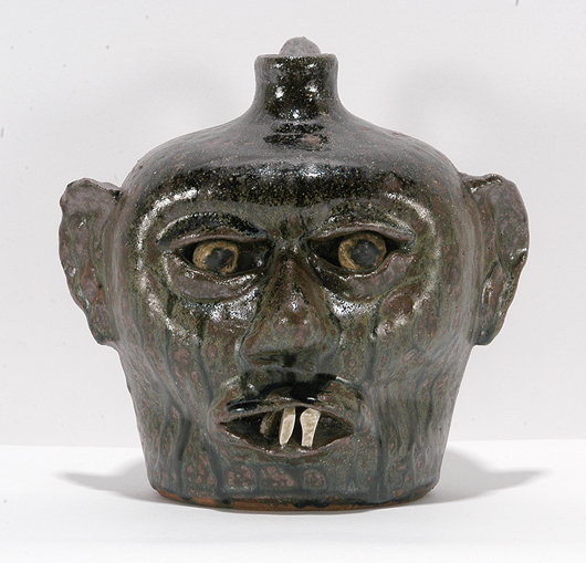 Lanier Meaders, rare Smithsonian china plate tooth face jug, circa 1960's, made for the Smithsonian Folk Life sale. Deep rich drip tobacco spit glaze, 8 inches high. Estimate: $3,000-$5,000. Slotin Auction imge.