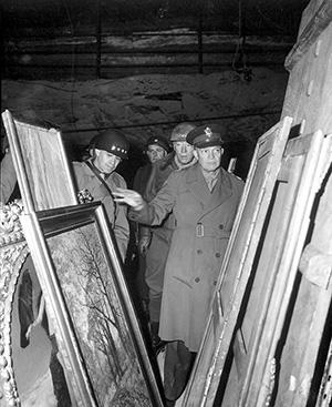 Gen. Dwight D. Eisenhower, Supreme Allied Commander, accompanied by Gen. Omar N. Bradley, and Lt. Gen. George S. Patton Jr., inspect art treasures stolen by Germans and hidden in salt mine in Germany in 1945. Image courtesy of Wikimedia Commons.