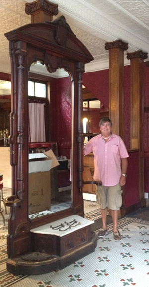 Auctioneer Tim Chapulis is dwarfed by a monumental marble-top hall tree standing 9 1/2 feet tall. Tim's Inc. image.
