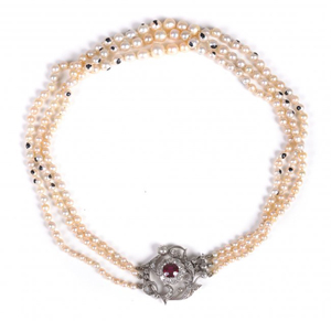 Three-strand natural and cultured pearl necklace composed of strands with 69, 73 and 69 pearls, attached to a scrolled foliate diamond clasp centered with an oval cut ruby and diamond flower head cluster. Estimate: £5,000–£7,000. Dreweatts & Bloomsbury image.