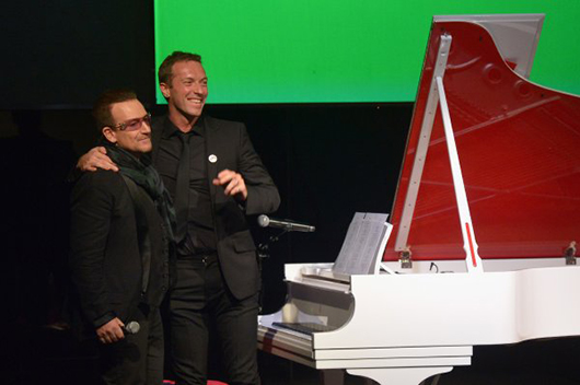 Bono (L) and Chris Martin perform onstage during Jony And Marc's (RED) Auction at Sotheby's on November 23, 2013 in New York City. The piano was subsequently auctioned for $1.9 million. Photo by Mike Coppola/Getty Images for (RED).
