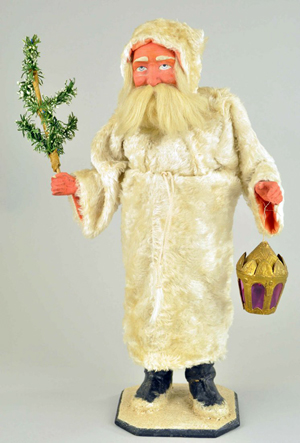 Large candy container depicting Father Christmas, Germany, composition feet, hands and face, carrying a Dresden lantern and a paper tree, 18 1/2 inches. Image courtesy of LiveAuctioneers.com Archive and Bertoia Auctions.
