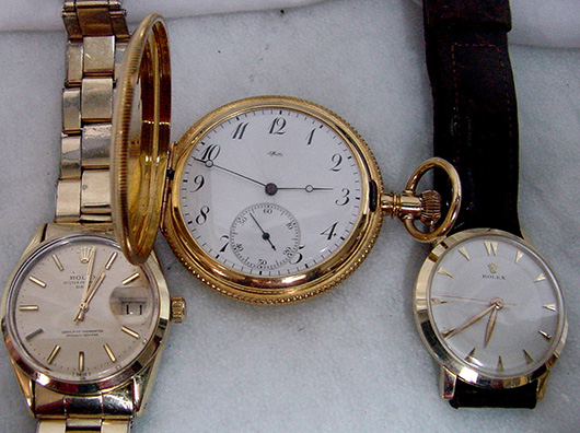 Two men's gold Rolex wristwatches (left and right) and an 18K gold Tiffany pocket watch. John W. Coker Auctions image.