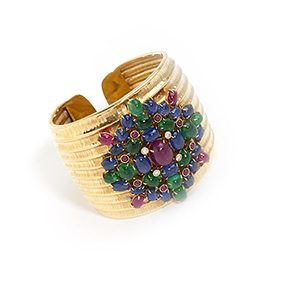 One of a number of striking bangles offered, this 18K gold bangle by Demner, set with rubies, sapphires and emeralds, realized $7,200 (estimate: $3,500-$4,500). John Moran Antique and Fine Art Auctioneers image.