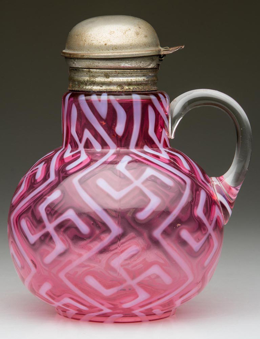 Lot 684: Swastika Indiana mold syrup pitcher, also in cranberry opalescent glass, Dugan Glass Co., circa 1904, 5 3/4 inches. Price realized: $3,737.50. Jeffrey S. Evans & Associates image.