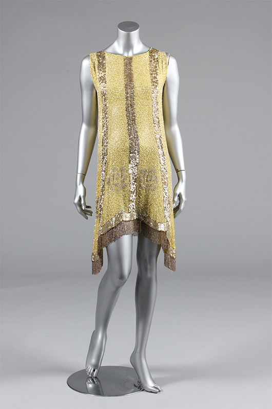 One of several flapper dresses offered: Beaded primrose-yellow muslin flapper dress, late 1920s, the ground covered with silver patterning, with small-beaded flowers, gold and silver sequined stripes, and gold beaded fringes. Estimate £300/500. From Kerry Taylor Auction's February 25, 2014 Vintage Fashion sale, London. Kerry Taylor Auctions image.