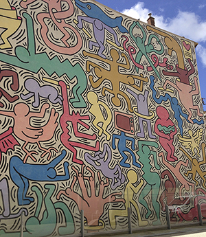Keith Haring's 'Tuttomondo' mural on the side of a church in Pisa, Italy. Photo by CutieKatie. This file is licensed under the Creative Commons Attribution-Share Alike 3.0 Unported license.