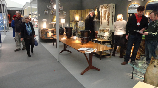 The stand of Holly Johnson Antiques at the British Antique Dealers' Fair in London, featuring a fine dining table dating from the early 1960s by the English Arts and Crafts-influenced designer Edward Barnsley (foreground), priced at £16,750 ($28,000). Image Auction Central News.