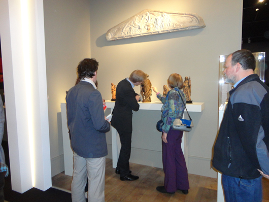 Visitors at the European Fine Art Fair in Maastricht investigating the gilding on an early European sculpture on the stand of London dealer Sam Fogg. Image Auction Central News.