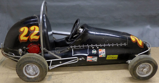 Vintage go-kart resembling a scaled-down 1930s/40s racer with colorful stickers and single roll bar, 78in long by 34in high. Sterling Auctions image