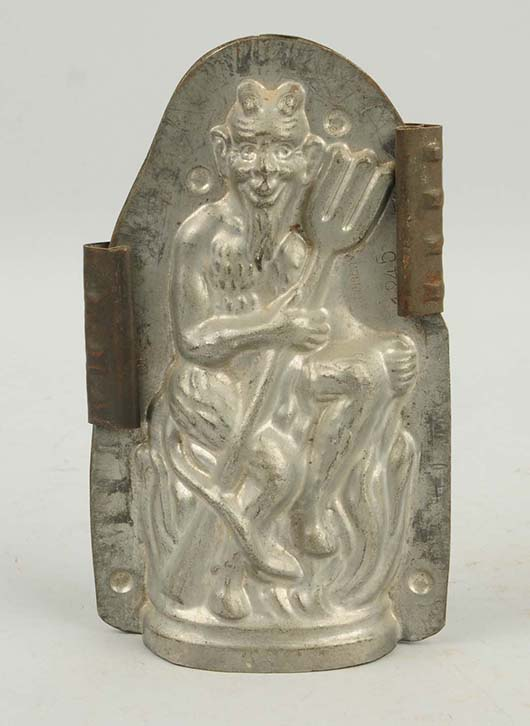 German chocolate candy mold depicting devil with trident pitchfork on bed of flames. Est. $300-$500. Morphy Auctions image