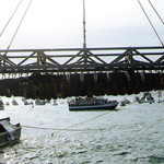 The Confederate submarine H.L. Hunley, suspended from a crane during her recovery from Charleston Harbor on Aug. 8, 2000. Image by Barbara Voulgaris, Naval Historical Center, courtesy of Wikimedia Commons.