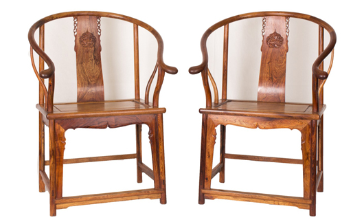 A pair of huanghuali chairs with delicate escutcheon splat back and exquisitely shaped arms, the seat supported by embellished front. Estimate: $16,000-$24,000. Linwoods Auctions image.