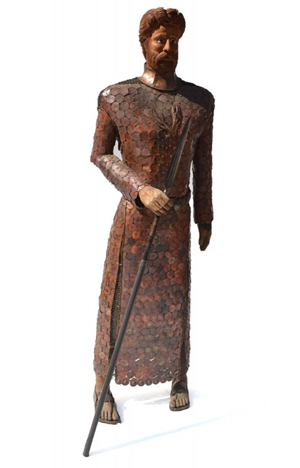 Larger than life mixed media sculpture of a knight wearing chain mail and a copper garment and holding lance. Roland Auctions image.