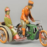 M & K tinplate clockwork motorcycle with sidecar and woman passenger, sold for $10,620. Bertoia Auctions image