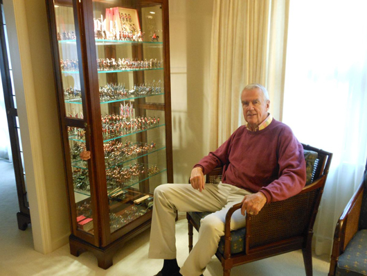 James A. Henderson, retired chairman and CEO of Cummins Engine Co. Inc., at home with prized pieces from his collection displayed in a showcase. Old Toy Soldier Auctions image