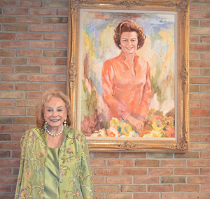 Painter Patricia Hill Burnett with her portrait of First Lady Betty Ford, which is now part of the permanent collection at the Gerald R. Ford Presidential Library. Image courtesy of the Gerald R. Ford Presidential Library