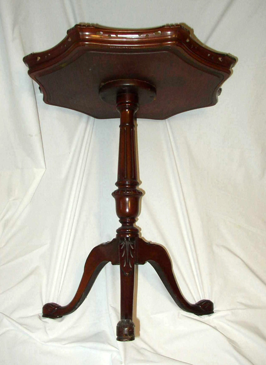 The turned and carved pedestal, legs and feet of the lamp table, like the edge of the top, are  made of gum, colored to look like mahogany.