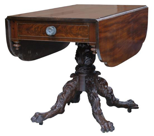 This Empire drop-leaf table, circa 8130, has as solid mahogany top and base with crotch cut mahogany veneer on the drawer front and skirt.