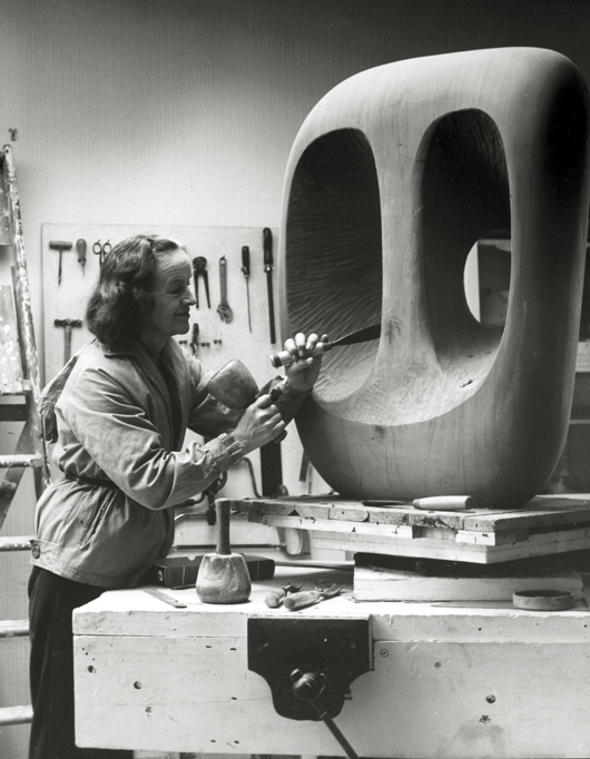 Barbara Hepworth in the Palais studio in 1963 with unfinished wood carving 'Hollow Form with White Interior.' Photograph by Val Wilmer, courtesy Bowness, Hepworth Estate.