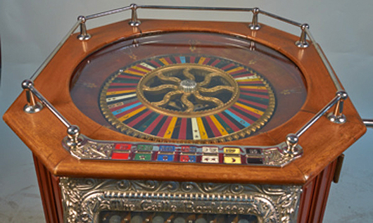 Top view of 1904 Caille roulette floor machine, mahogany with ornate repousse, nickel-plated embellishments. Provenance: the William F. Harrah collection. Morphy Auctions/Victorian Casino Antiques image
