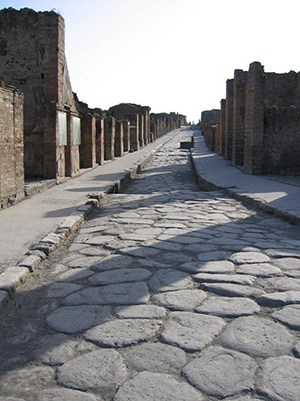 A narrow Pompeii street paved in stone. Image by Paul Vlaar. This file is licensed under the Creative Commons Attribution-ShareAlike 3.0 Unported License.