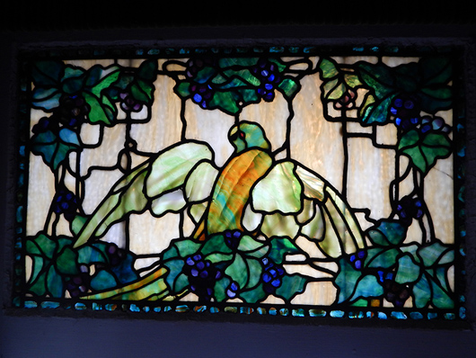 Stained-glass window depicting colorful parrot amid grapes and vines, origin: Morgantown, W.Va., from the estate of opera singer Frances Yeend and James Benner to be auctioned Aug. 29-30. Joe R. Pyle Auction image