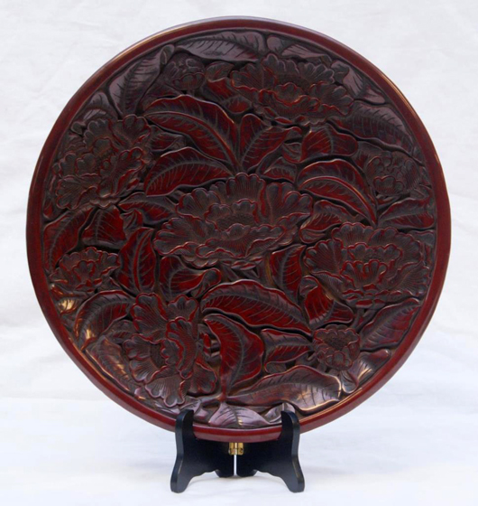 Chinese 17th century red cinnabar lacquered plate depicting lotus blossoms in a deep relief design (est. $10,000-$15,000). Elite Decorative Arts image.