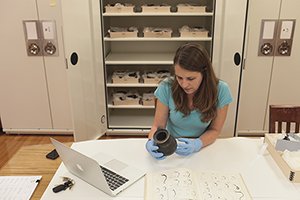 A University of Missouri researcher studies an Ancient Roman artifact. Photo by Nic Benner