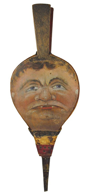A man's face is a clever decoration on a bellows used to fan flames in a fireplace. The rare 19th-century bellows sold at auction for $2,700.
