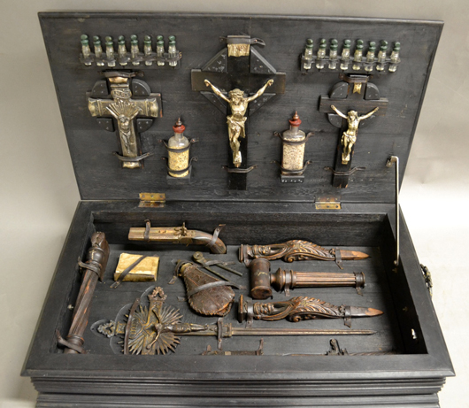 Vampire-killing kit with wood stakes, silver crucifixes and other accouterments in coffin-shape box. Sterling Associates image
