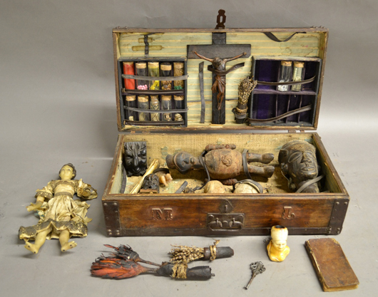 Nineteenth-century voodoo priestess box with various hexing paraphernalia, including wax doll, skull, claw, mystical herbs, etc. Sterling Associates image
