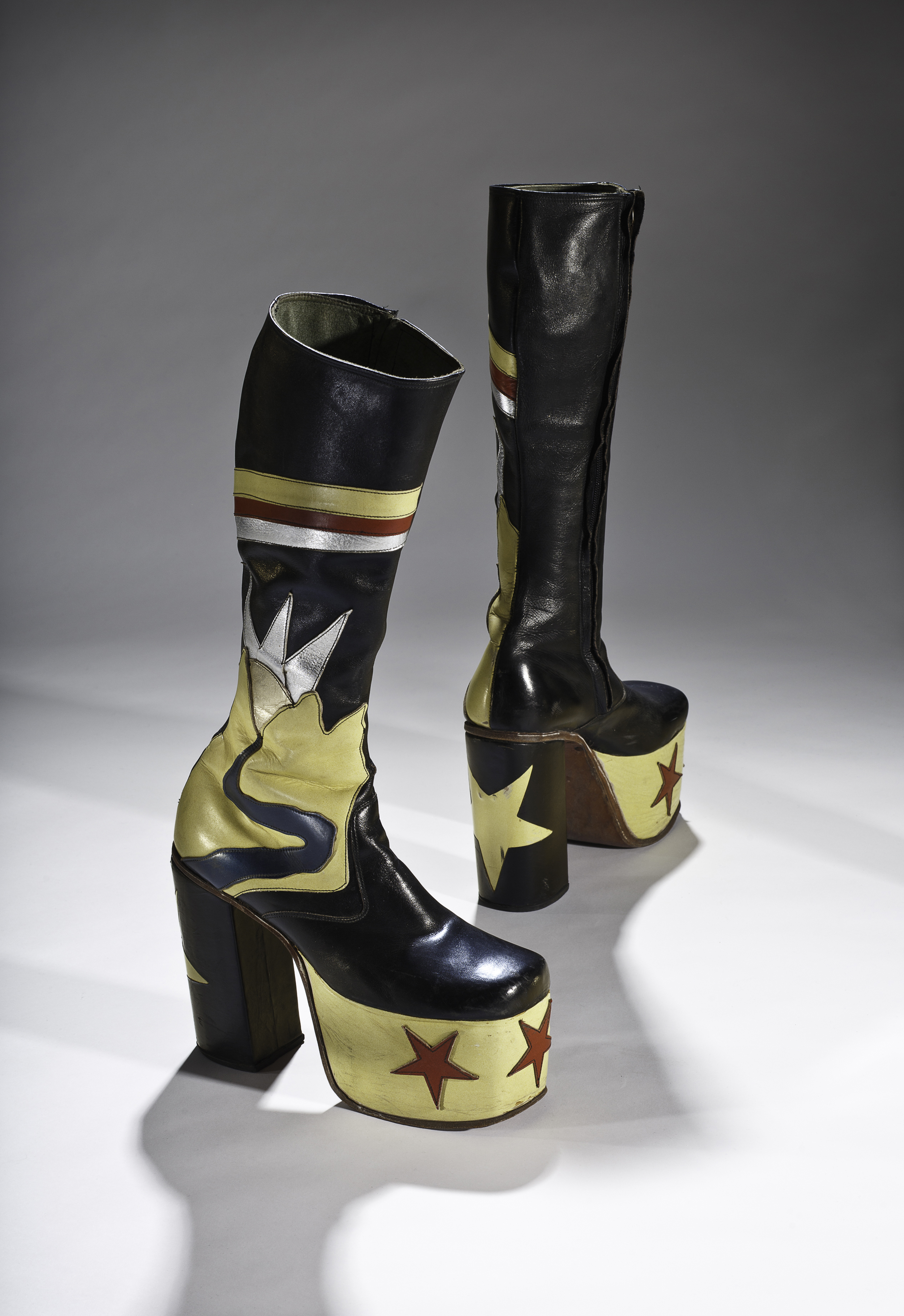 Toronto shoemaker Master John made these men's platform boots complete with 5 1/2-inch heels, appliquéd stars, and veritable landscape in leather. In the 1970s, some men followed the lead of rock stars in adopting lavish personal adornment and elevating shoes cultivating a persona at once dandyish and hyper-masculine. Collection of the Bata Shoe Museum. Photo credit: Image © 2015 Bata Shoe Museum, Toronto, Canada