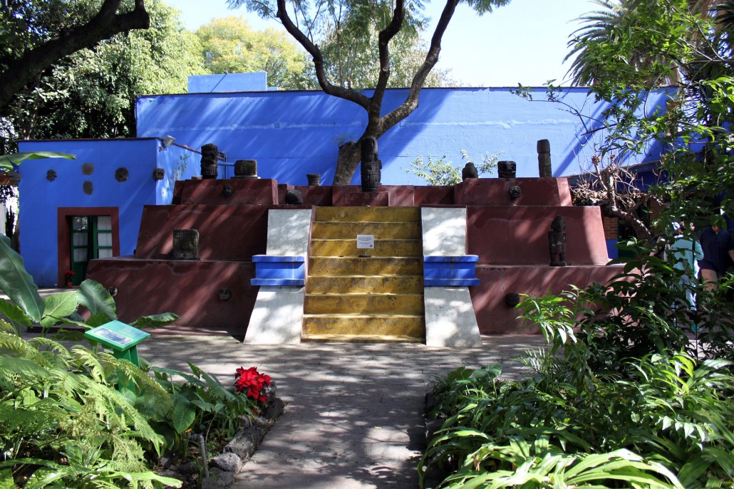 A tomb in the form of a pyramid is the focal point of the garden at Frida Kahlo Museum in the Coyoacan suburb of Mexico City. The museum was Frida Kahlo's residence and studio, and is known as Casa Azul, or Blue House. December 22, 2013 photo by Anagoria, licensed under the Creative Commons Attribution 3.0 Unported license.