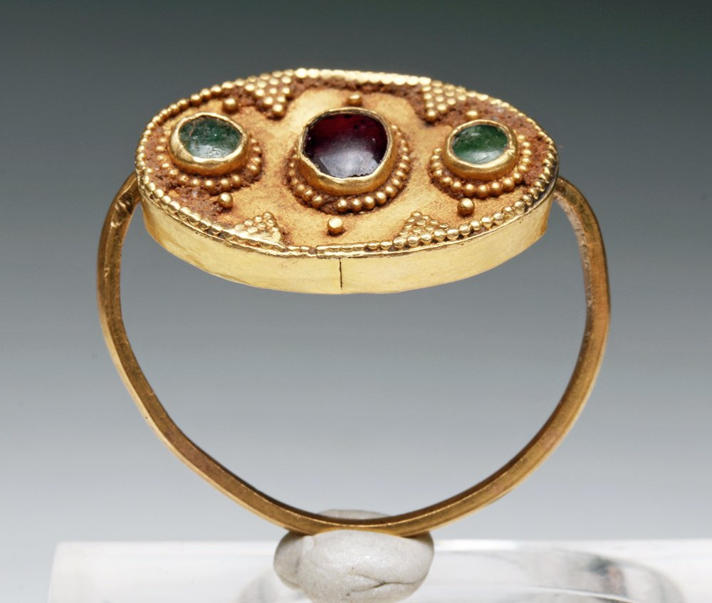Viking 18K gold ring with central cabochon garnet and flanking emerald cabochons, circa 9th to 12th centuries CE, estimate $20,000-$25,000. Artemis Gallery image