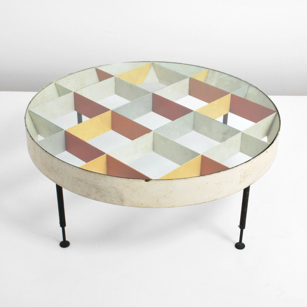 Ponti experimented with a design for a grid-structured circular coffee table throughout his career. There are rare early examples made of wood. By the 1950s, it had evolved into an enameled metal 'Harlequin' table illustrated in a mid-decade issue of 'Domus.' Colors change from blue and yellow to red and yellow as the viewer walks around the table. Courtesy Palm Beach Modern Auctions.