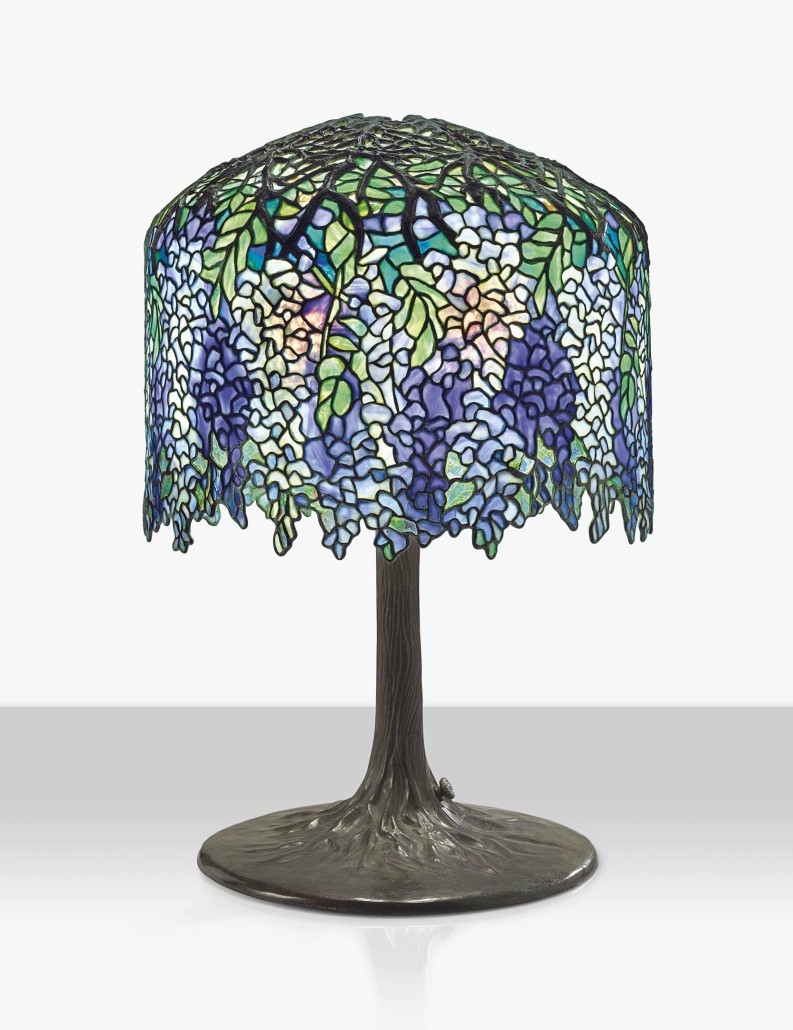 Tiffany used wisteria flower patterns for lamps of various sizes as well as large landscape windows. Glass colors vary from shade to shade. Collectors value examples with vivid hues of deep purple, blue and green. Courtesy Christie's