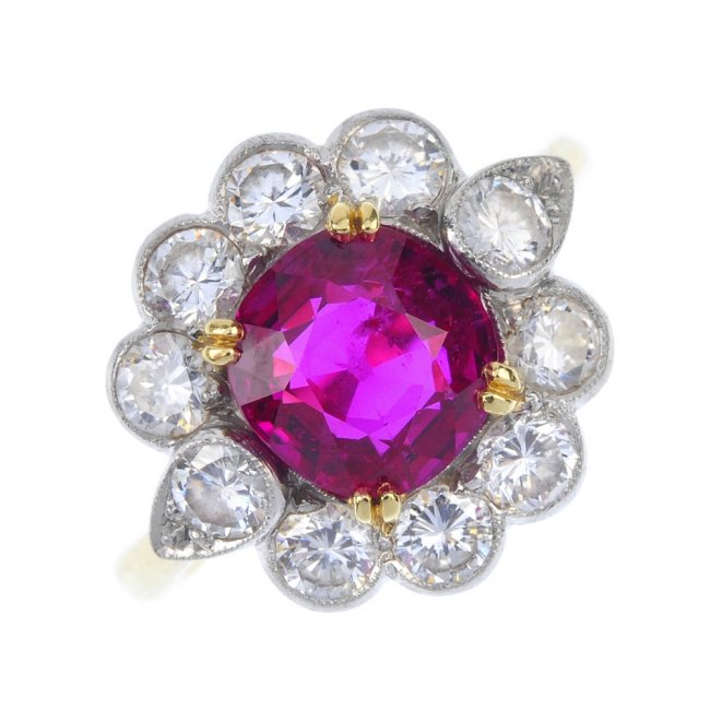 An 18ct gold Burmese ruby and diamond floral cluster ring. The cushion-shape ruby weighs approximately 2.80 carats. Fellows image