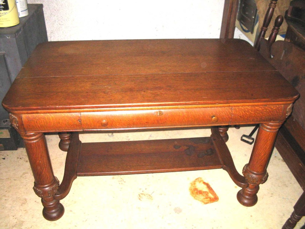 This library table demonstrates some of the conservation methods used late in the Golden Oak period. The drawer front, skirt and legs are veneered in quarter cut oak instead of being made of solid quarter cut oak. The top is solid flat cut oak boards and the emblems are applied, machine made appliques rather than hand carved.