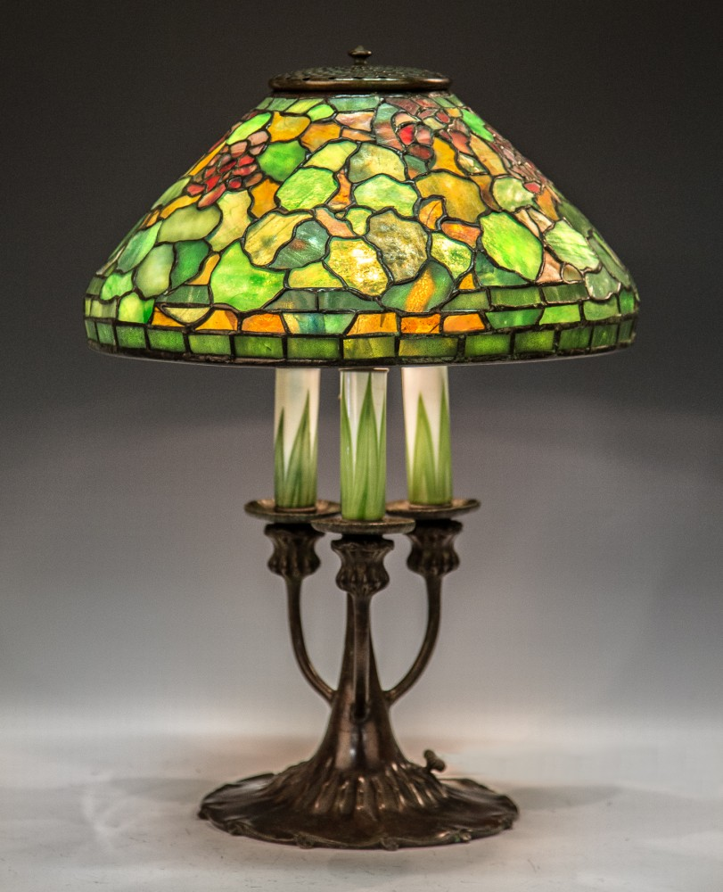 Rare Tiffany Studios leaded glass Geranium lamp with a signed shade and three-arm bronze and art glass candlestick base. Price realized: $52,325. Cottone Auctions image
