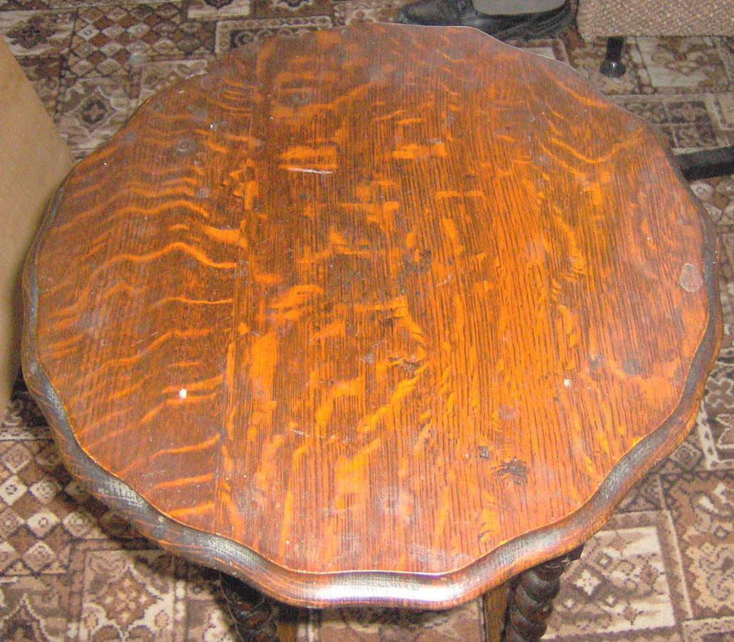 """This turn of the 20th century oak set is typical of mail order furniture of the period. The table has a quarter sawn oak veneer top, veneered skirt, veneered pedestal over solid oak, veneered base, turned under """"Colonial"""" style feet borrowed from the Late Classicism style of the 1840s and press back flat cut solid oak chairs."""