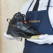 Sotheby's set a new world record for sneakers by selling a Kanye West-worn 2008 prototype pair for $1.8m.