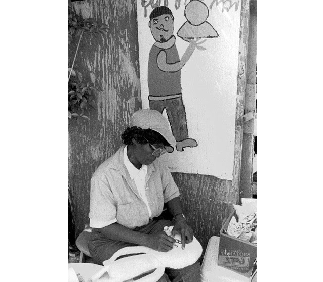 "Ruby ""Miss Ruby"" Williams lives and paints beneath a wooden lean-to from which she can oversee the sale of the fruits and vegetables that she grows."