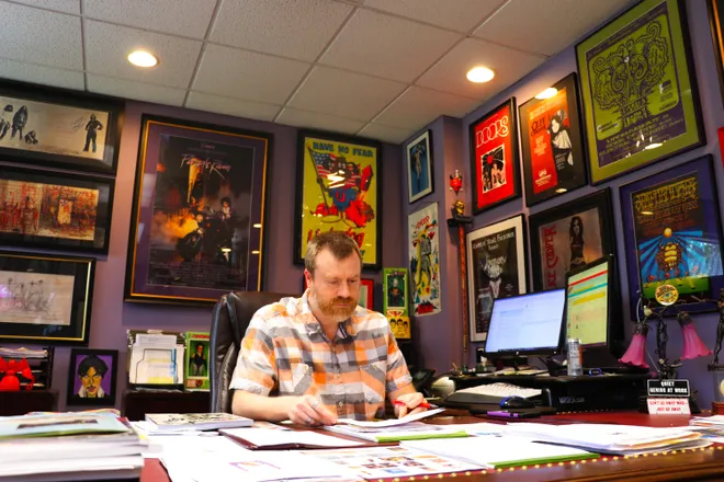 Alex Winter working in his office at Hake's, surrounded by some of his collections, including records.