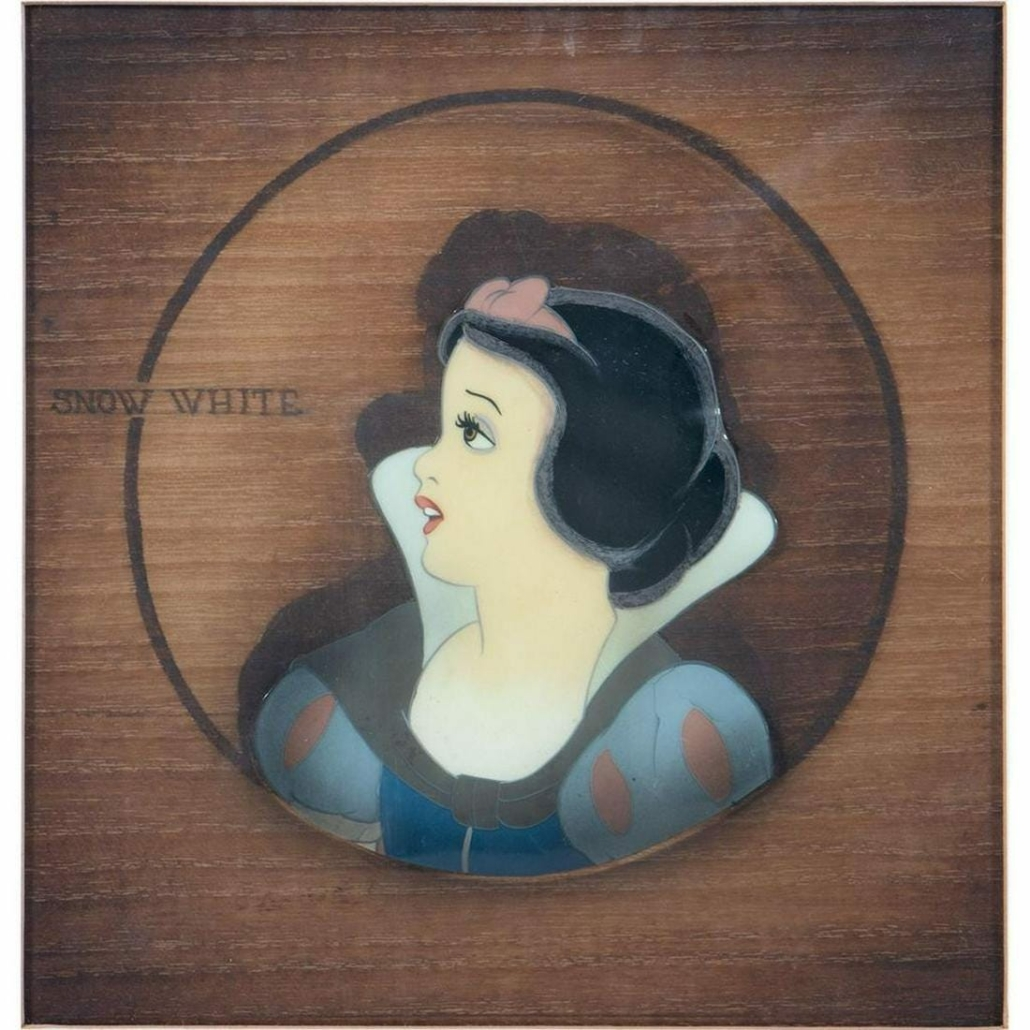 Original animation cel from 'Snow White and the Seven Dwarfs,' mounted on a woodgrain background, estimated at $1,000-$1,500
